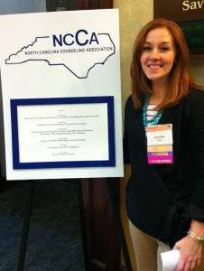 Jenny Niles, Class of 2012, Stands Next to NCCA Conference Sign Before Presenting with Instructor Heidi Robinson ('11) and Classmate Brian Calhoun ('12)